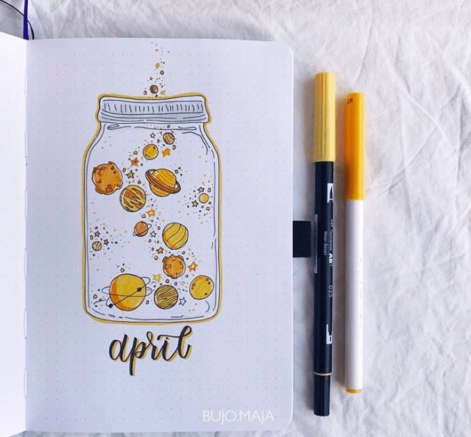 Yellow space themed solar system in a jar in April Bullet Journal cover page